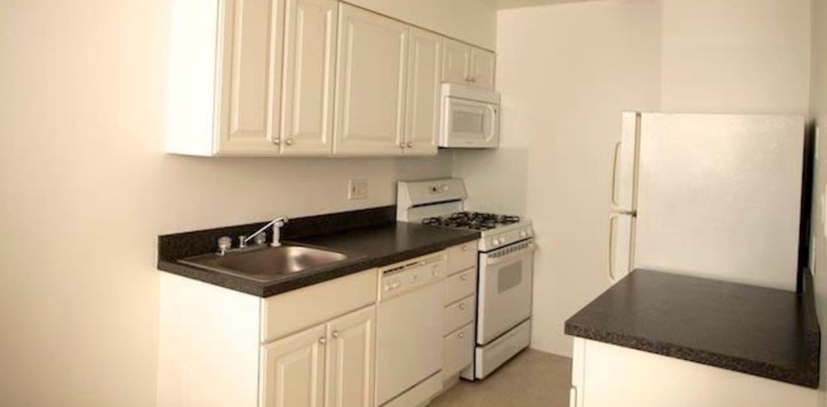 White kitchen cabinets with nice black countertops at Marina Park Apartments in Collingswood, New Jersey