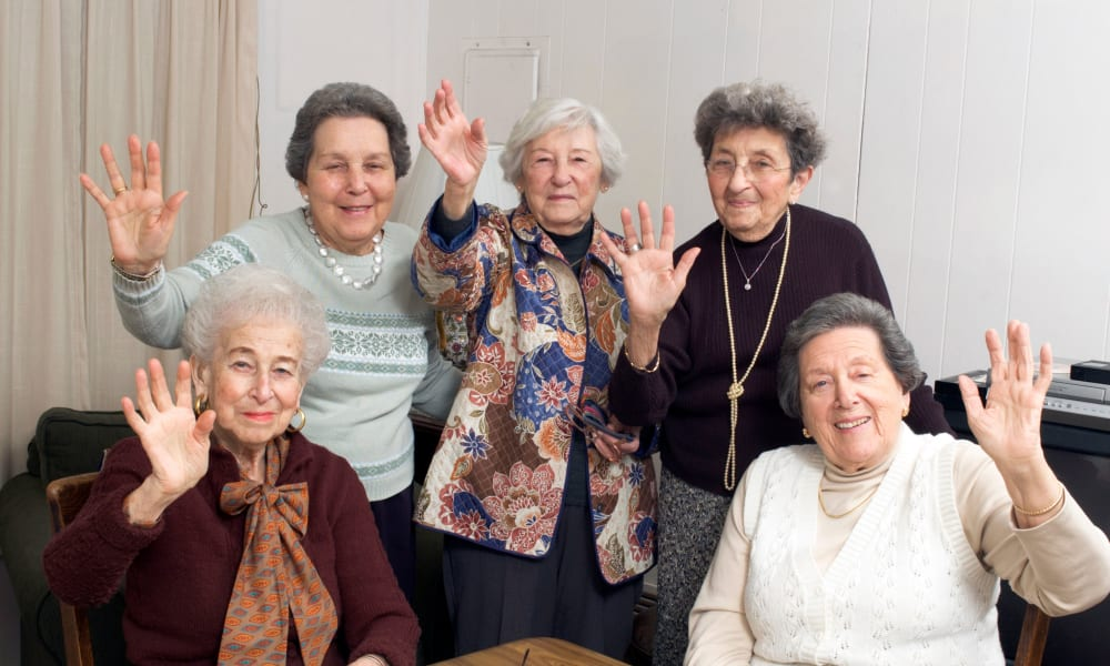 A group of residents wave at the camera at Absaroka Senior Living in Cody, Wyoming