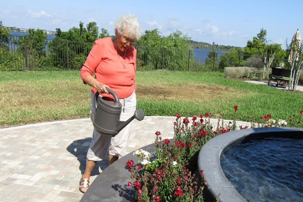 Resident watering flowers at Azpira at Windermere in Windermere, Florida