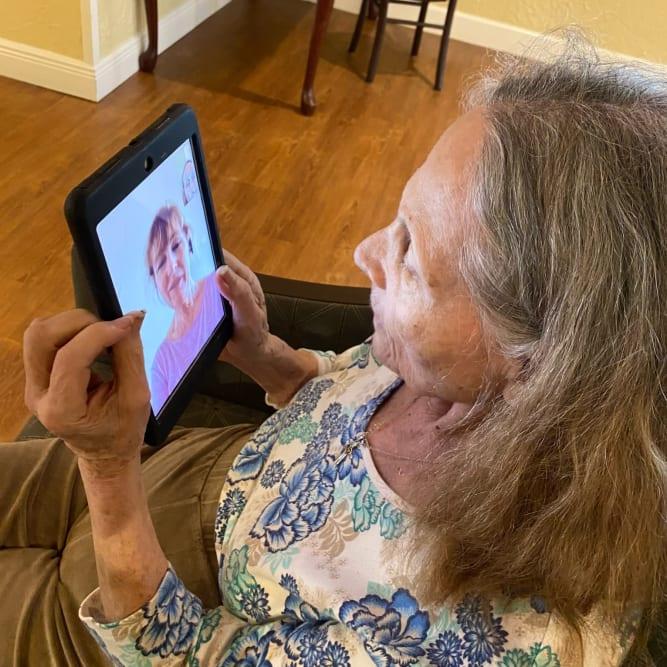 Resident video chatting relative at Grand Villa of Altamonte Springs in Altamonte Springs, Florida