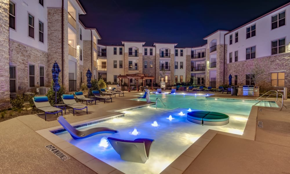 Awesome pool at night with lights in the water at Bellrock Upper North in Haltom City, Texas