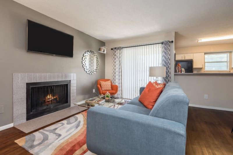 Living room area with cozy fireplace and tv mounted to the wall at The Carling on Frankford in Carrollton, Texas