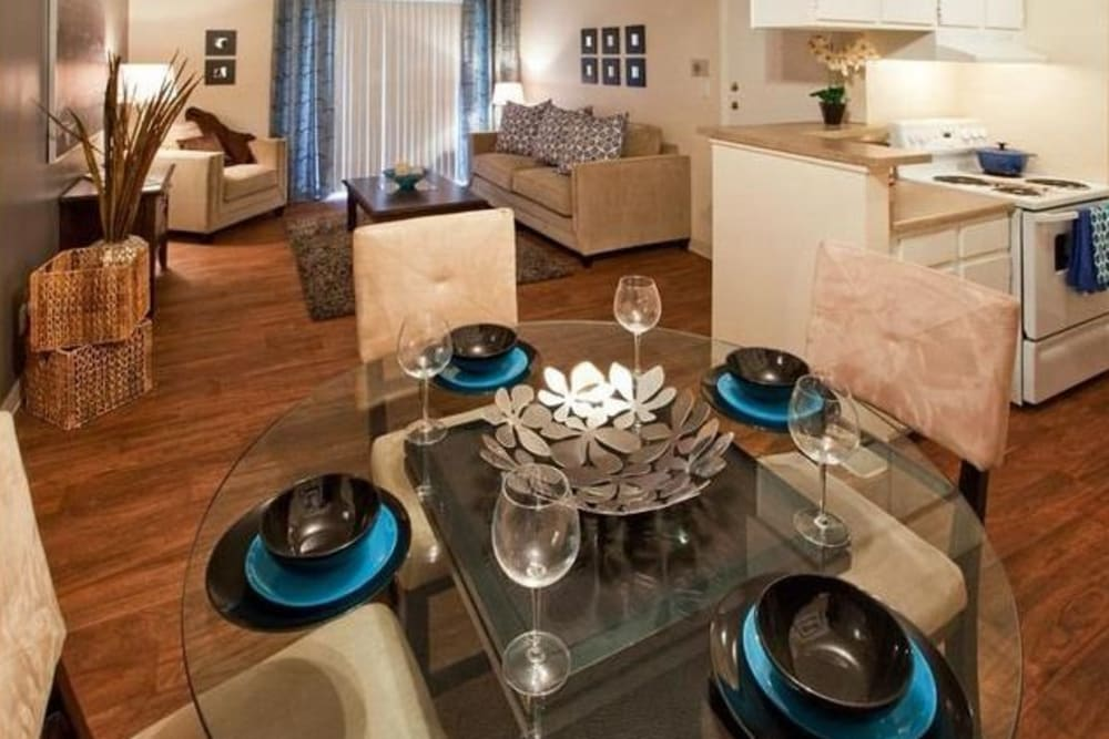 Dining table and spacious living room at Hampden Heights Apartments in Denver, Colorado with ample natural light