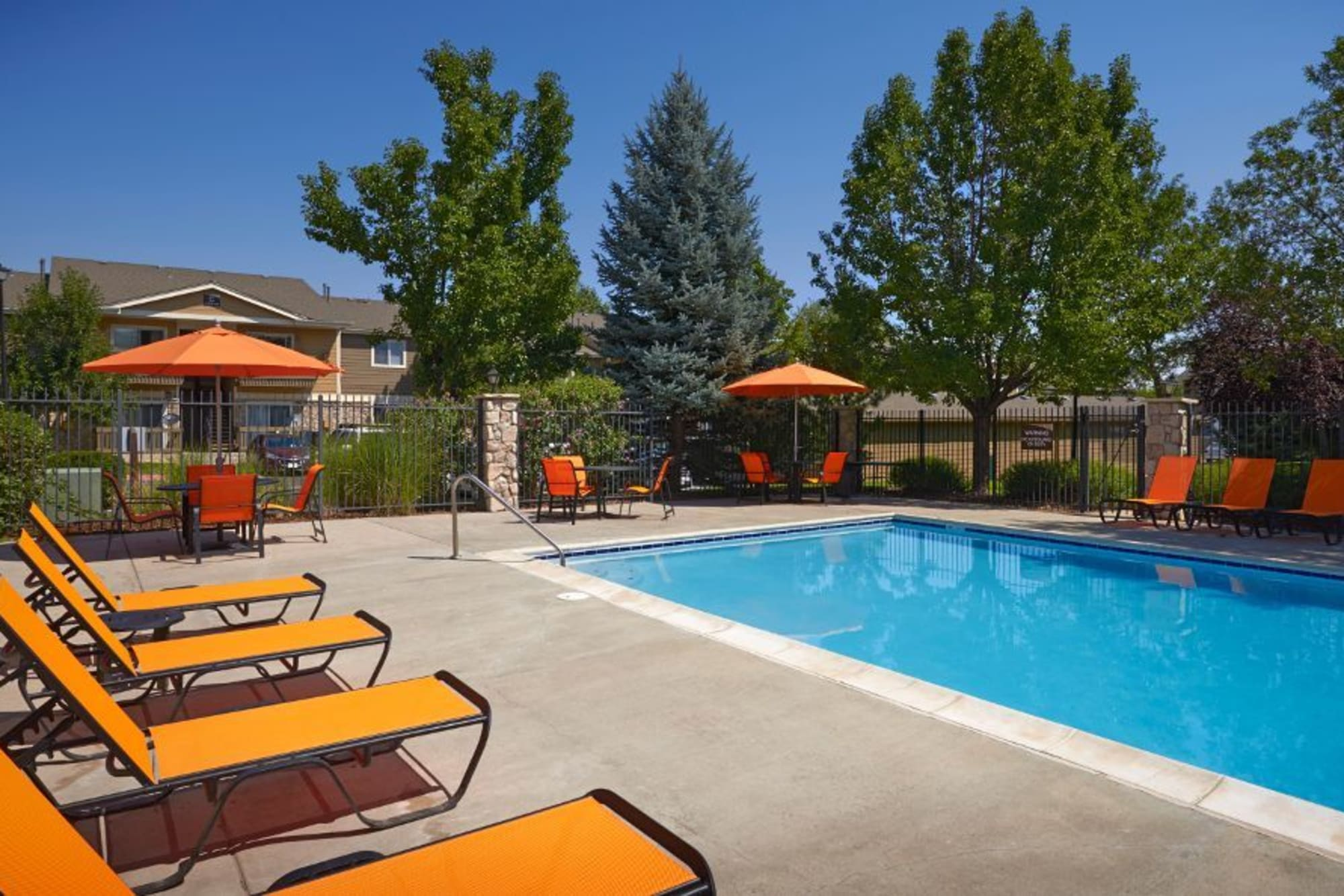 Sparkling pool with lounge chairs at Crossroads at City Center Apartments in Aurora, Colorado
