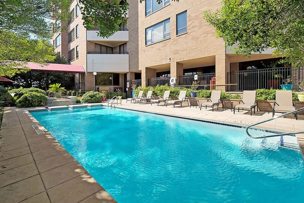 Relax in the swimming pool at The Enclave at 1550 Apartments in San Antonio, TX