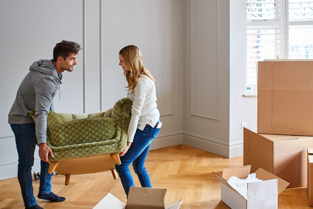 A couple arranging furniture at their new apartment near Trojan Storage in Salinas, California
