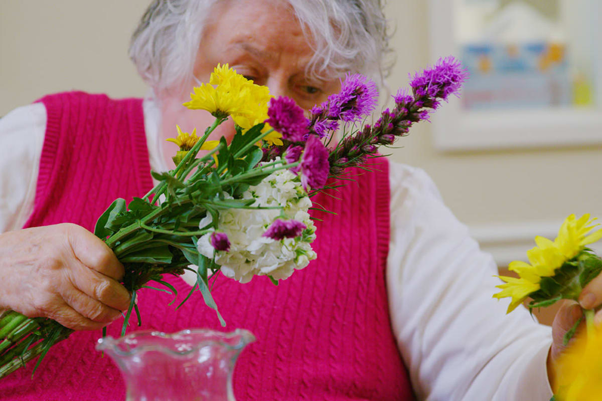 Woman creating floral arrangement at Farmington Square Eugene in Eugene, Oregon
