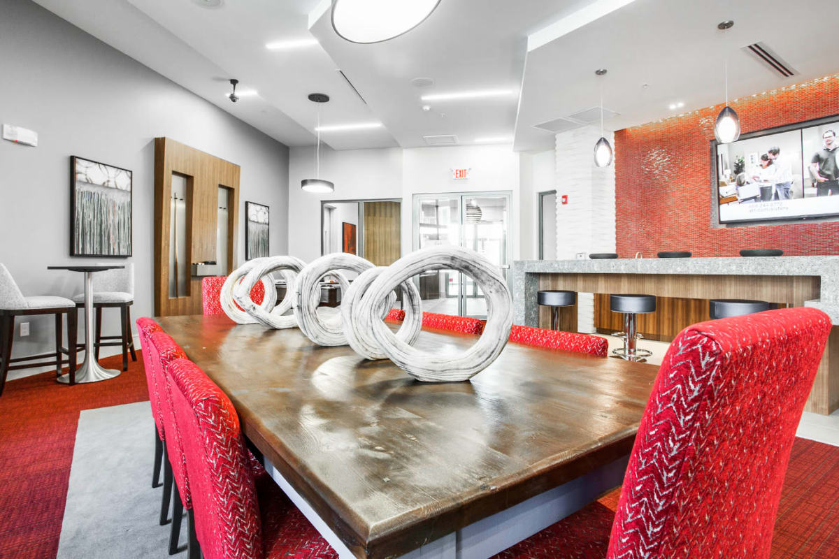 Large dining table for eight with red, cushioned chairs in community room at Marq Midtown 205 in Charlotte, North Carolina