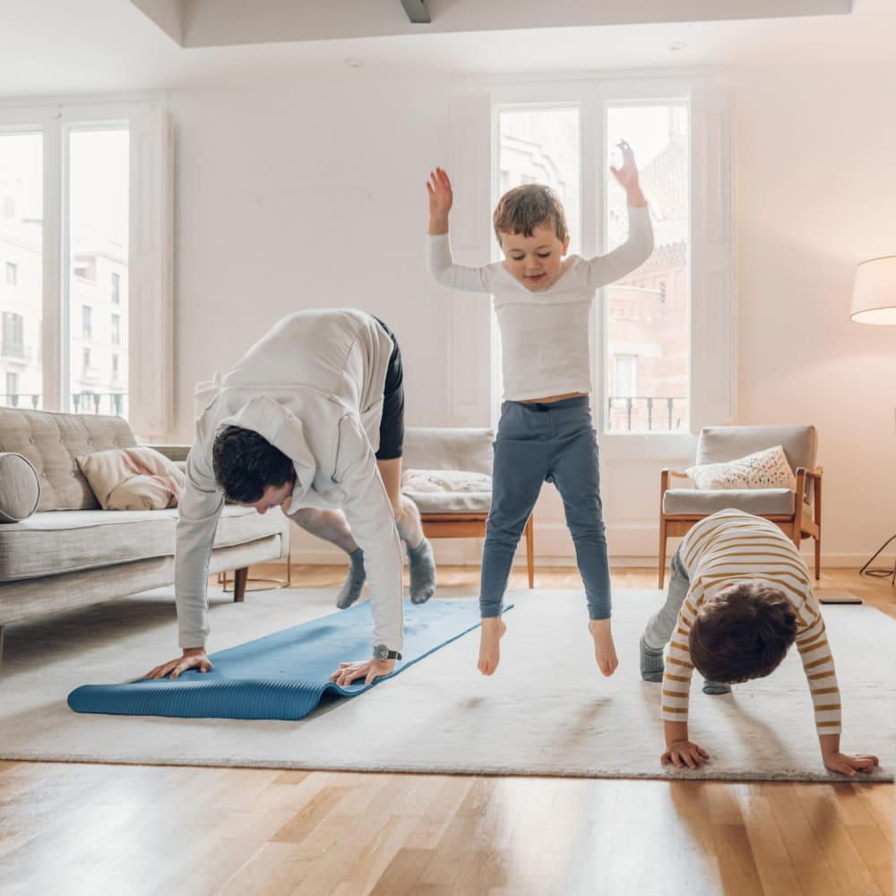 Family doing yoga together in their living room at Mandalane Apartments in Wheeling, Illinois