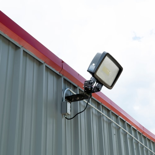 Floodlight mounted on a grey storage unit wall at Red Dot Storage in Denham Springs, Louisiana