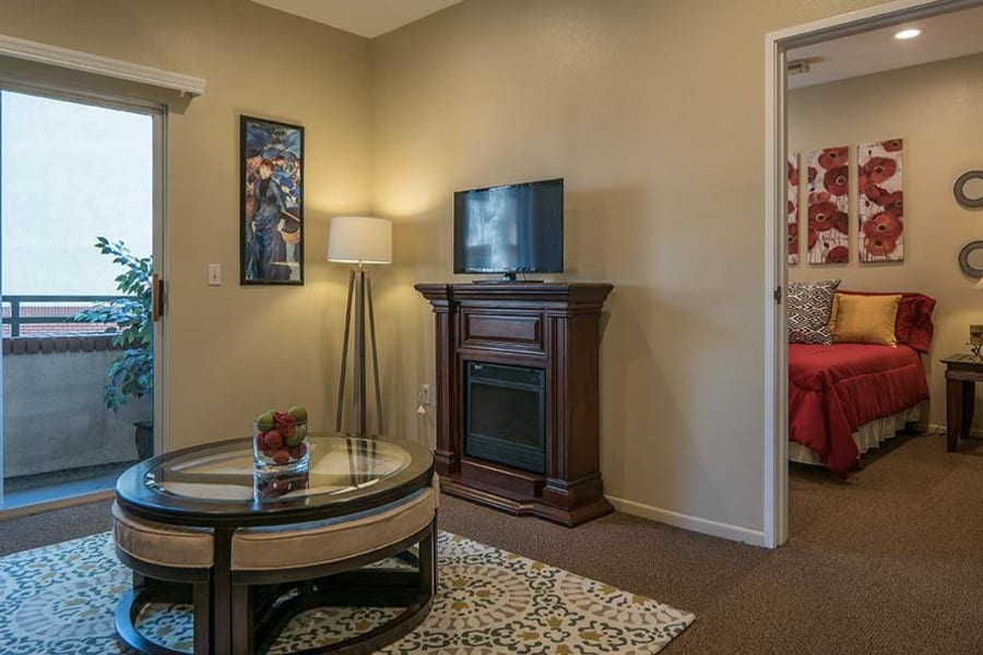 Living area and partial view of the adjacent bedroom in one of our memory care suites at Carmel Village in Fountain Valley, California