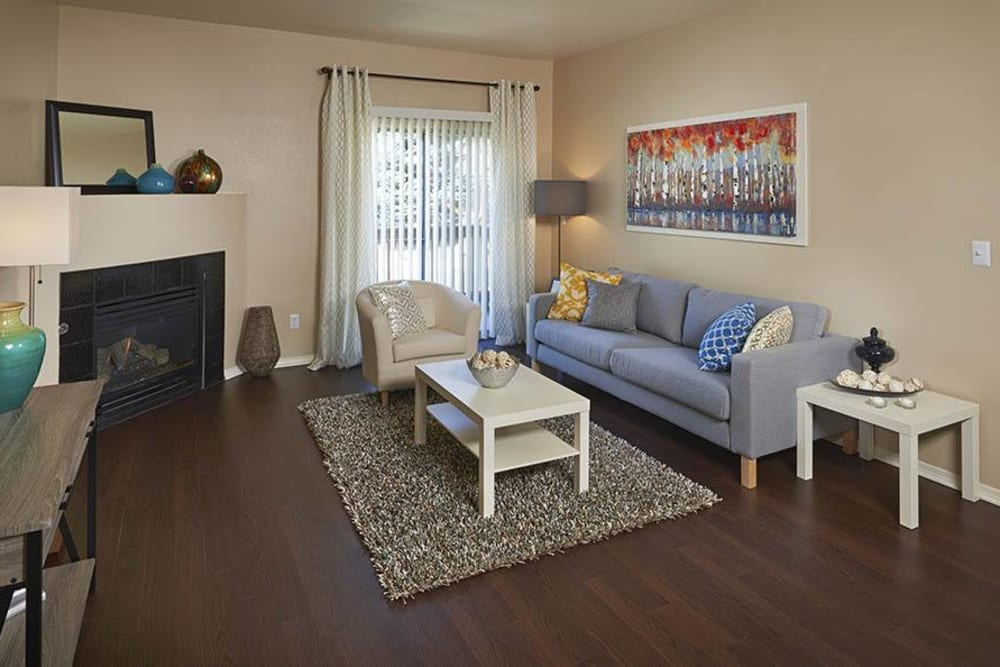 Living room with wood-style flooring at Crossroads at City Center Apartments in Aurora, Colorado