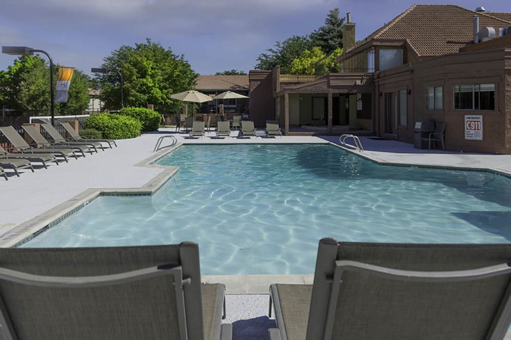 Beautiful resort-style swimming pool with lounge chairs at Shadowbrook Apartments in West Valley City, Utah