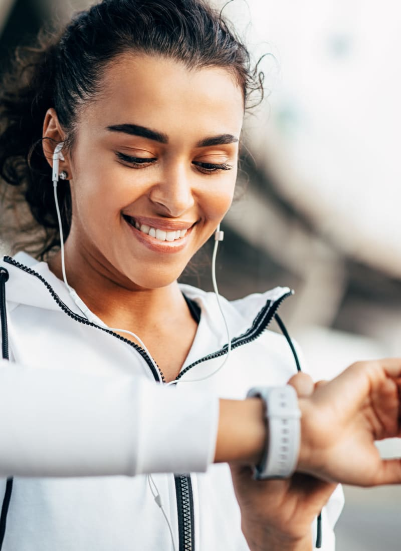 Young woman setting her smart watch while exercising near Marquis at Carmel Commons in Charlotte, North Carolina