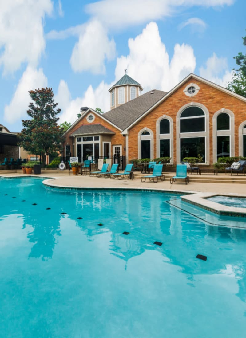 Sparkling pool with hot tub and turquoise lounge chairs Marquis at Kingwood in Kingwood, Texas