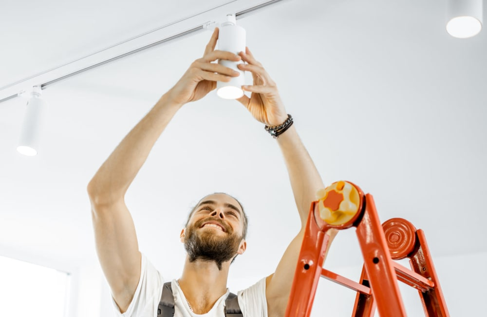 Resident replacing light bulb in their Olympus Property apartment