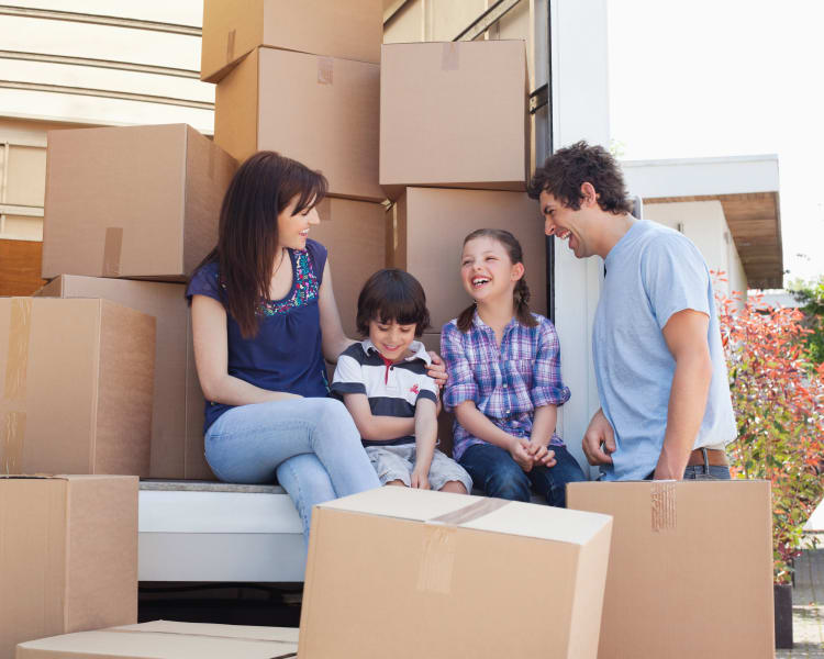 Happy family with a full moving truck ready to store their belongings at Star Security Storage