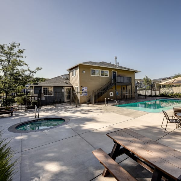 Swimming pool with a sundeck and picnic tables at Northwind Apartments in Reno, Nevada