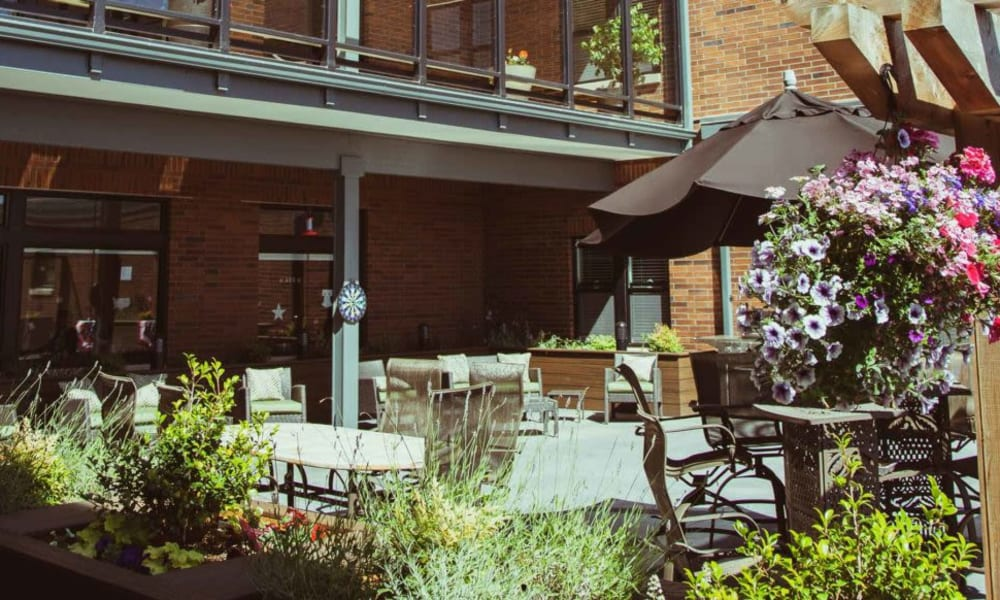 Patio with covered seating at Quail Park Memory Care Residences of West Seattle in Seattle, Washington