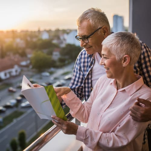 A future resident couple reading a brochure about The Vista in Esquimalt, British Columbia.