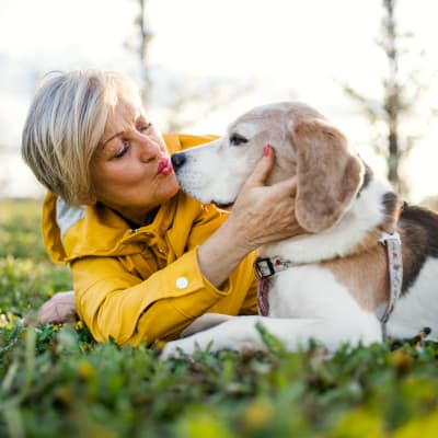 A woman and her dog lay in the grass at Chandler's Square Retirement Community in Anacortes, Washington
