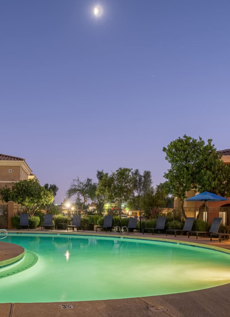 Pool with lounge chairs at sunset at Alante at the Islands in Chandler, Arizona