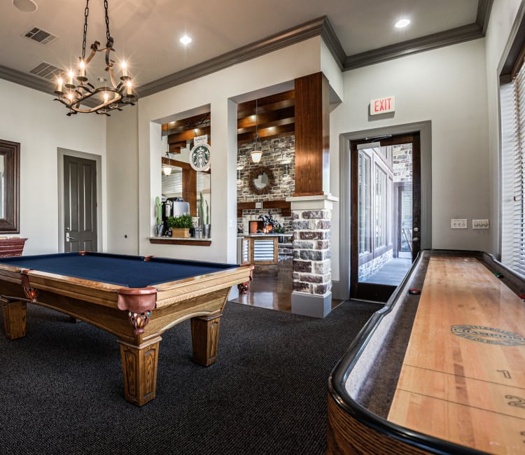 Billiards and shuffleboard tables in the game room at Ranch ThreeOFive in Arlington, Texas