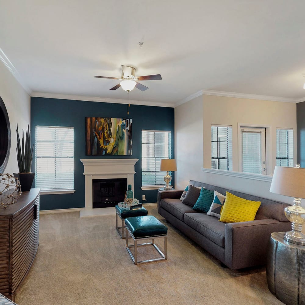 Plush carpeting and a fireplace in a model home's living area at Oaks Riverchase in Coppell, Texas