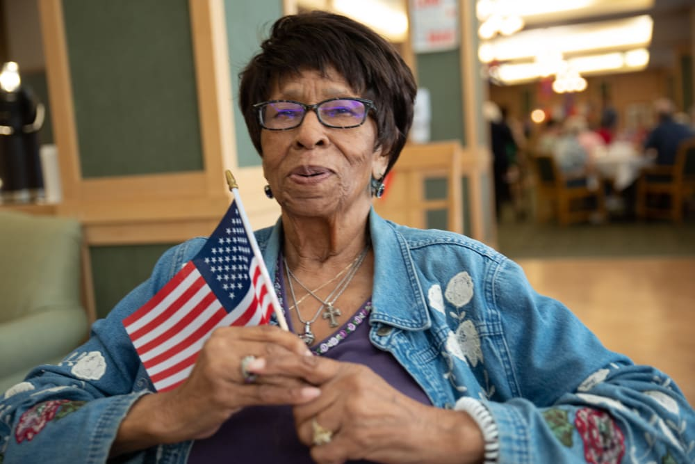 Resident waving flag at Merrill Gardens at Renton Centre in Renton, Washington.