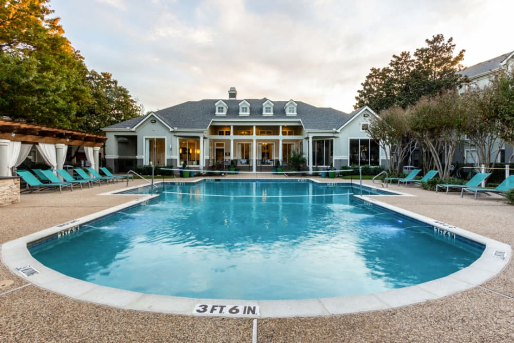Pool with volleyball net and clubhouse at Marquis at Stonegate in Fort Worth, Texas