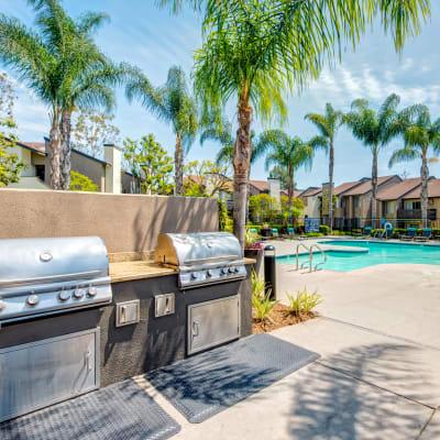 Barbecue area with gas grills near the swimming pool at Sofi Laguna Hills in Laguna Hills, California