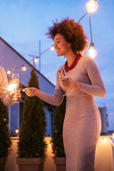 Resident lighting a sparkler at dusk on her private balcony at Solera at City Centre in Palm Beach Gardens, Florida