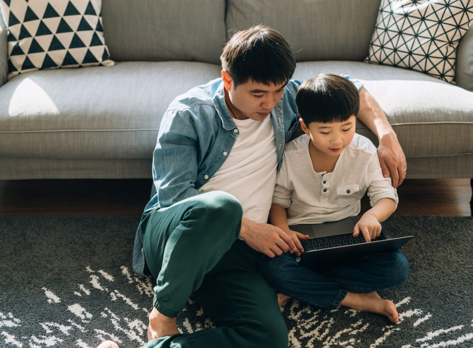Resident father and son surf online together at Sofi at 50 Forest in Stamford, Connecticut