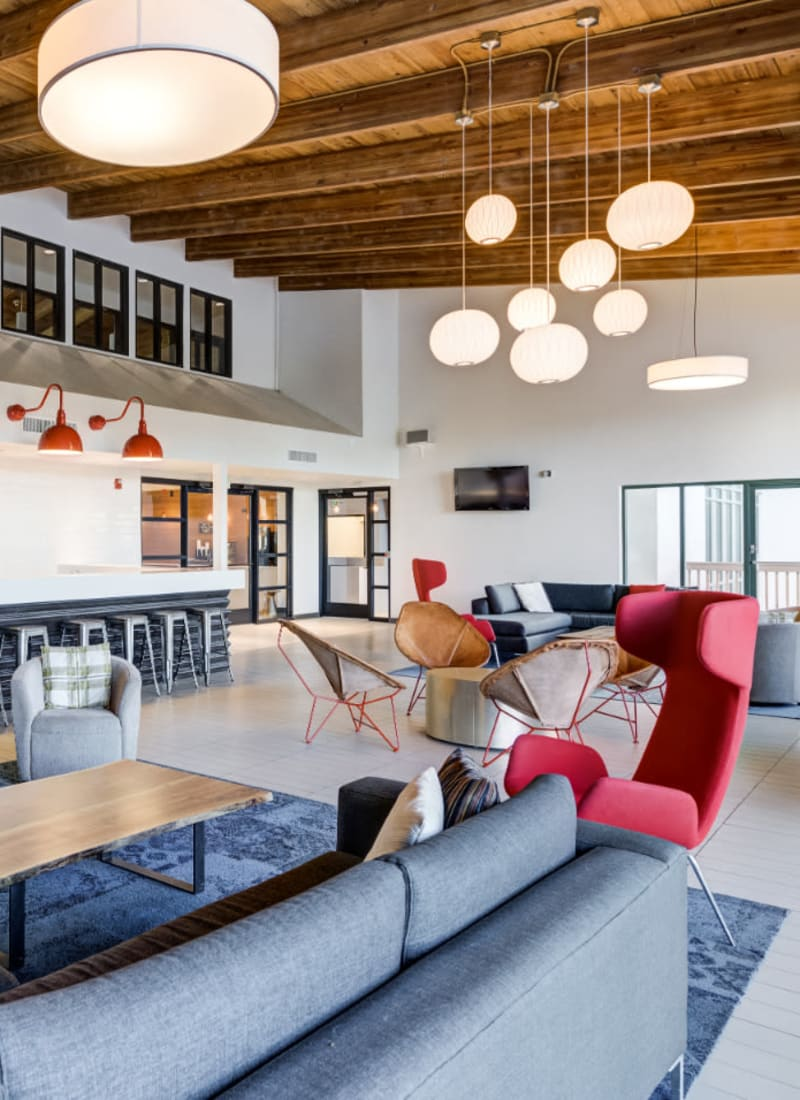 Community clubhouse with lounge area, fireplace, and kitchen area at Ashford Belmar in Lakewood, Colorado
