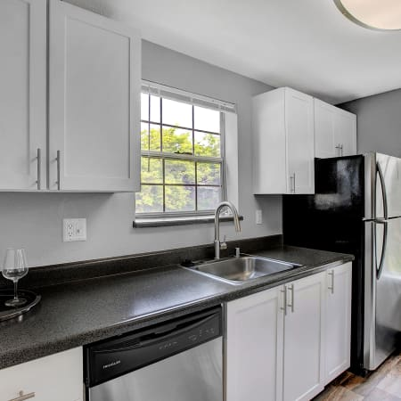 White renovated kitchen with stainless steel appliances at Waters Edge Apartments in Kent