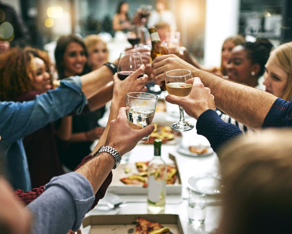 Group of resident friends out for a meal at their favorite restaurant and raising a toast to the good life at Domus on the Boulevard in Mountain View, California