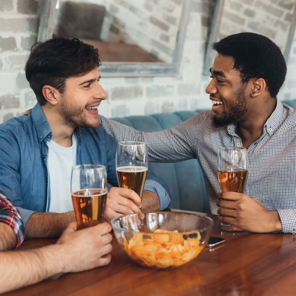 Residents catching up over beers and snacks at a pub near Olympus at Ross in Dallas, Texas