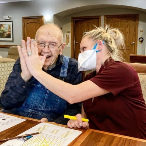 A masked team member high-fiving a resident at Glen Carr House Memory Care in Derby, Kansas