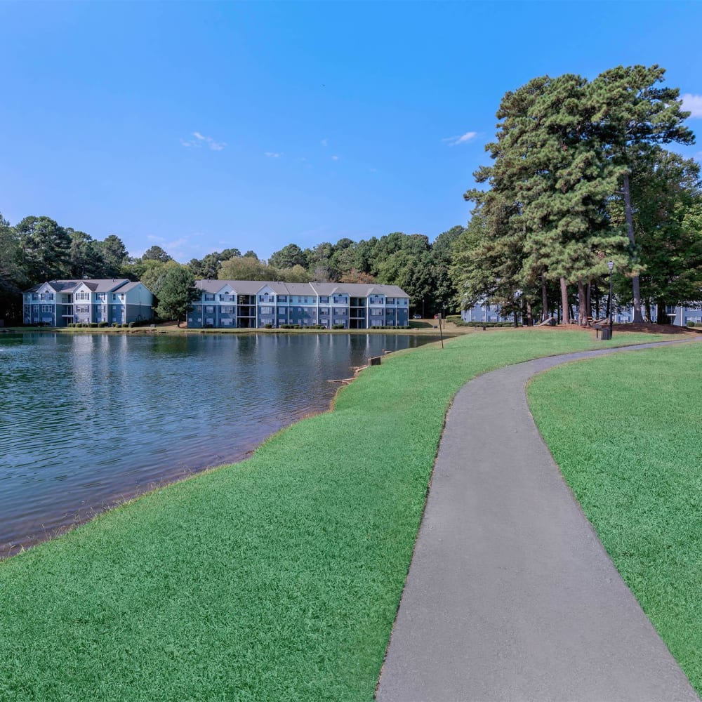 Pathway amid beautifully maintained grass along the lake at The Bentley at Marietta in Marietta, Georgia