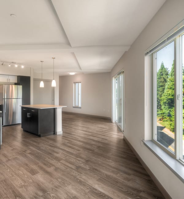 Kitchen with island, hardwood flooring throughout, and a large open living space at Tria Apartments in Newcastle,
