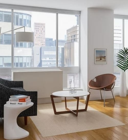 A living room with wood-style flooring with floor-to-ceiling windows at The Metropolis in New York, New York
