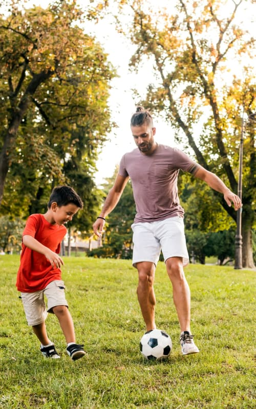 A resident playing soccer with his son near Town Park Villas in Tampa, Florida