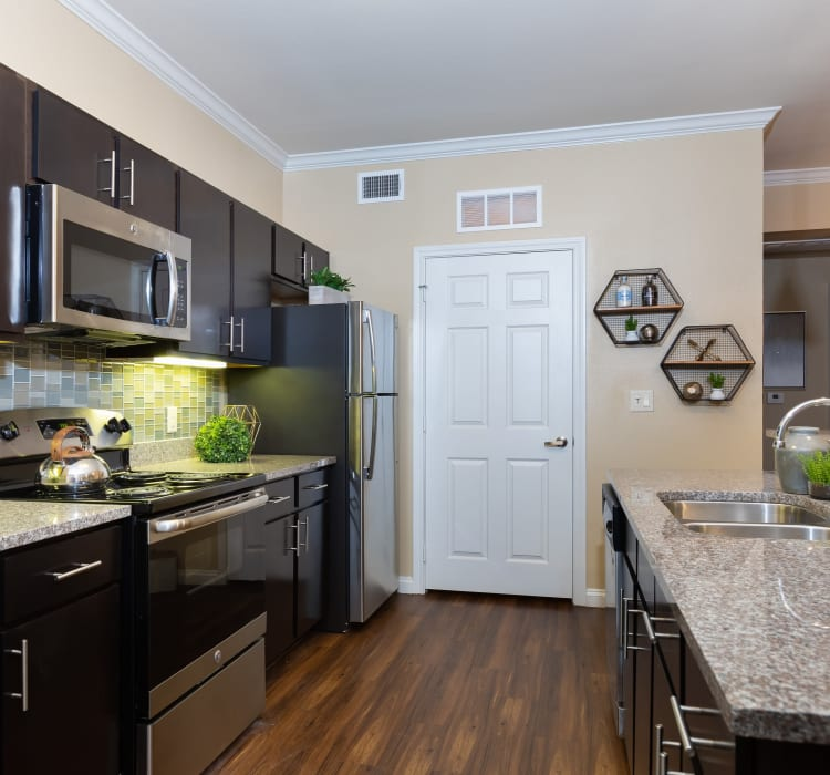 Dark wood cabinetry and a breakfast bar in a model home's kitchen at Hilltops in Conroe, Texas