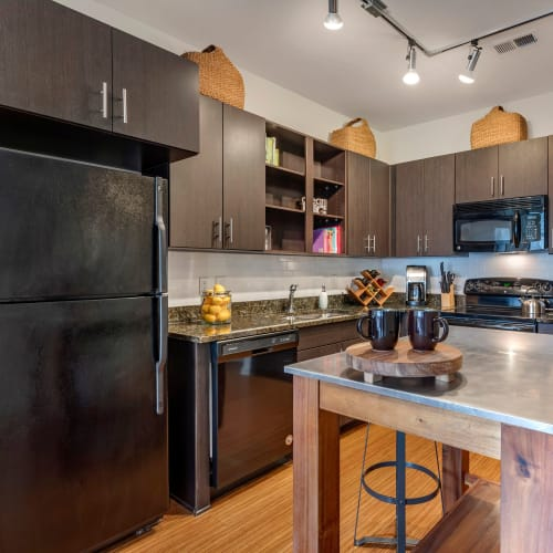 Model home's kitchen with an island and black appliances at Olympus Midtown in Nashville, Tennessee