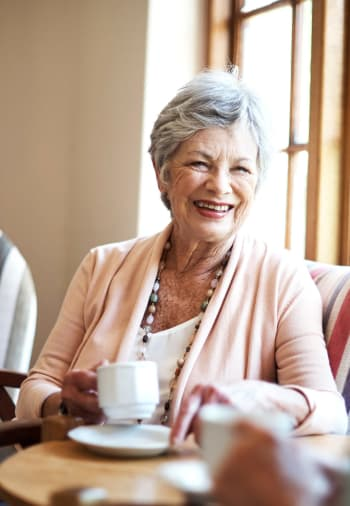 A resident enjoying a cup of coffee at Claiborne Senior Living.