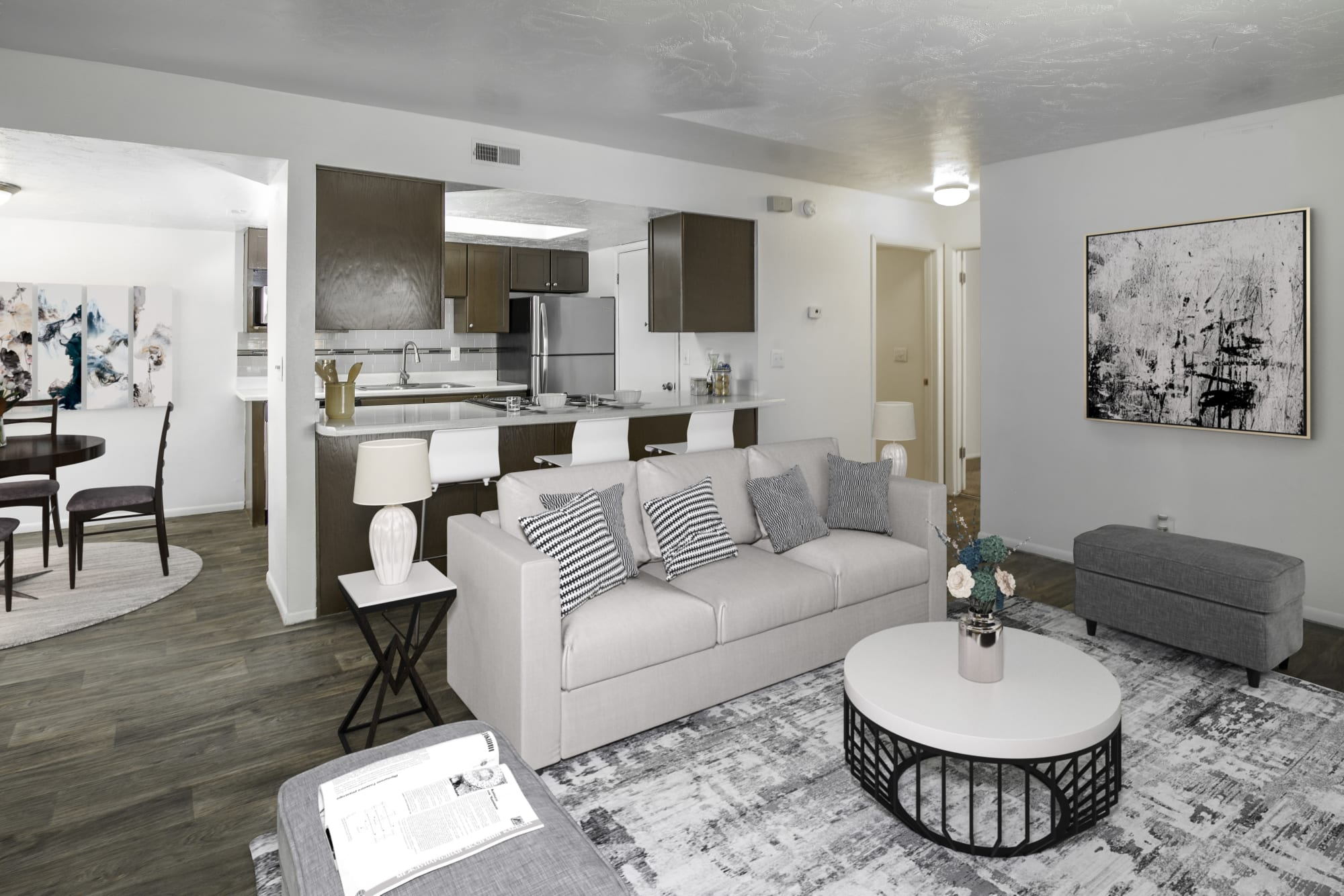 An open floor plan with the kitchen and dining room overlooking the living room at Windgate Apartments in Bountiful, Utah