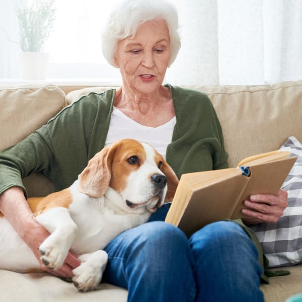 Woman with dog reading a book at Kenmore Senior Living in Kenmore, Washington