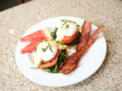 Eggs Benedict served with a side of Watermelon and Bacon at The Gardens at Park Balboa