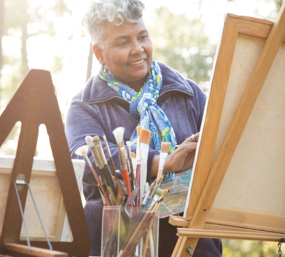 Resident painting a picture on an easel at Bishop Place Senior Living in Pullman, Washington