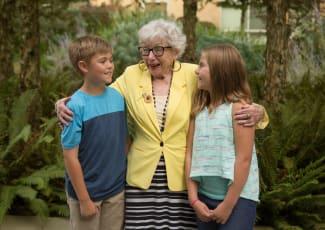 senior resident hugging grand children